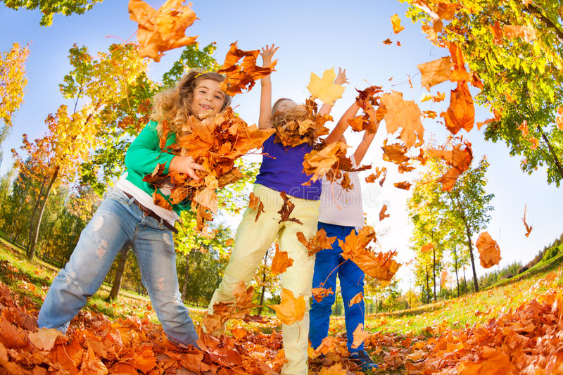 Kids playing with thrown leaves in the forest. Together during beautiful autumn sunny day royalty free stock photo