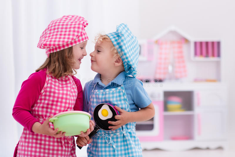 Kids playing with toy kitchen. Little girl and boy in chef hat and apron cooking fried eggs in toy kitchen. Wooden toys for young children. Kids play and cook at stock photography