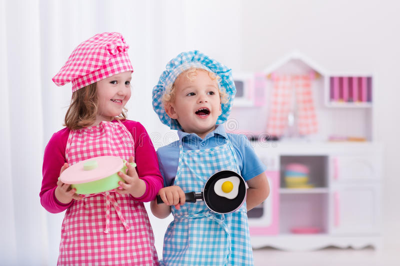 Kids playing with toy kitchen. Little girl and boy in chef hat and apron cooking fried eggs in toy kitchen. Wooden toys for young children. Kids play and cook at stock images