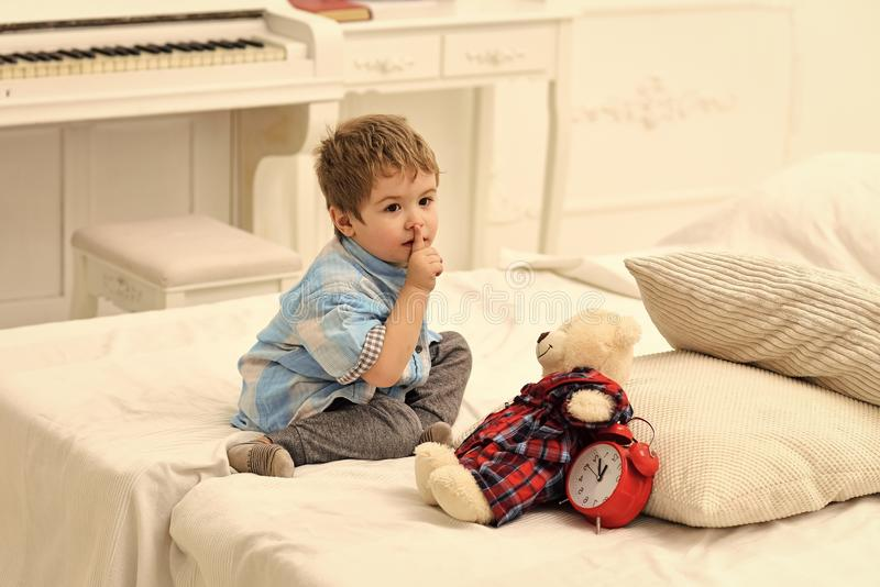 Kids playing with toys. Child in bedroom with silence gesture. Kid put plush bear near pillows and alarm clock, luxury royalty free stock image