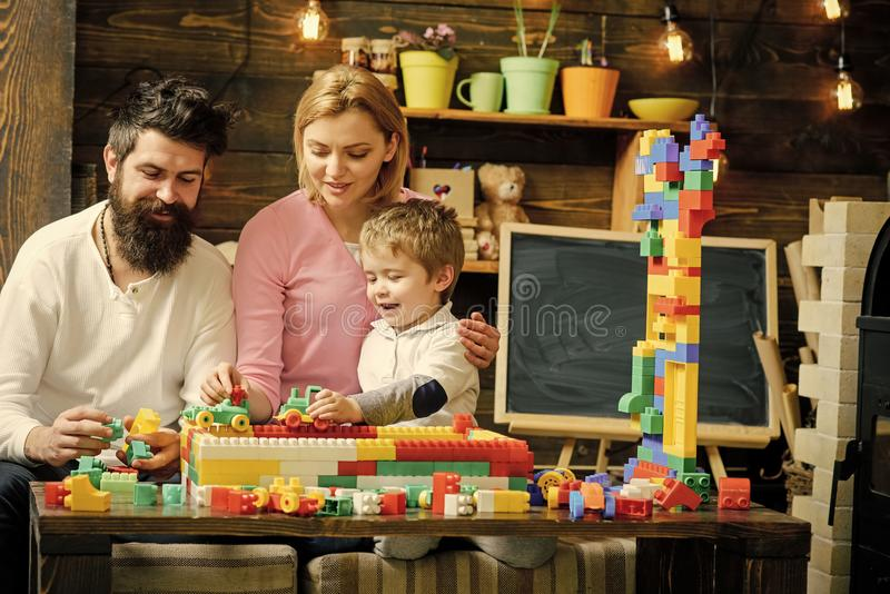 Kids playing with toys. Lovely family in playroom. Mom and kid playing with cars on race track out of plastic blocks stock image