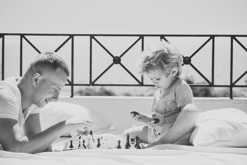 Smart toddler concept. Parent play chess with kid on terrace on sunny day. Kids playing with toys. Dad with child play royalty free stock photography