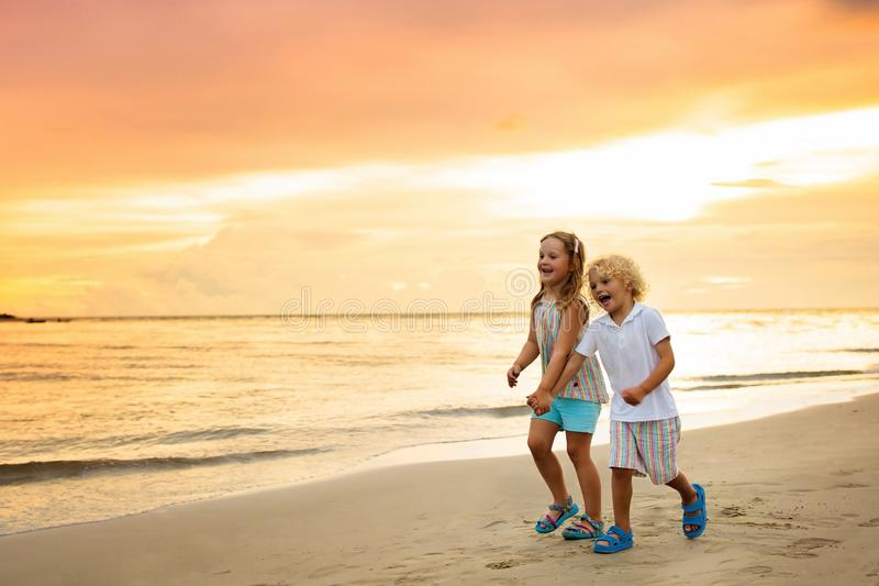 Kids on tropical beach. Children playing at sea. Kids playing on tropical beach. Little boy and girl run at sea shore at sunset. Family summer vacation stock images