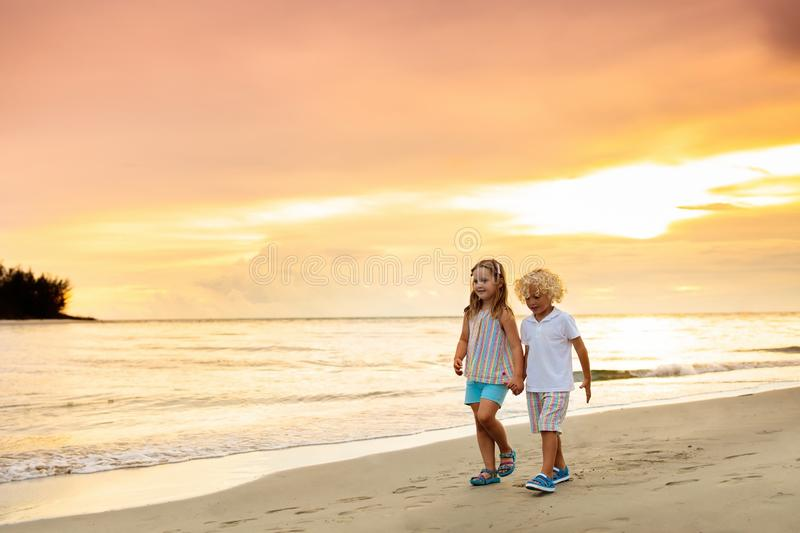 Kids on tropical beach. Children playing at sea. Kids playing on tropical beach. Little boy and girl run at sea shore at sunset. Family summer vacation royalty free stock image