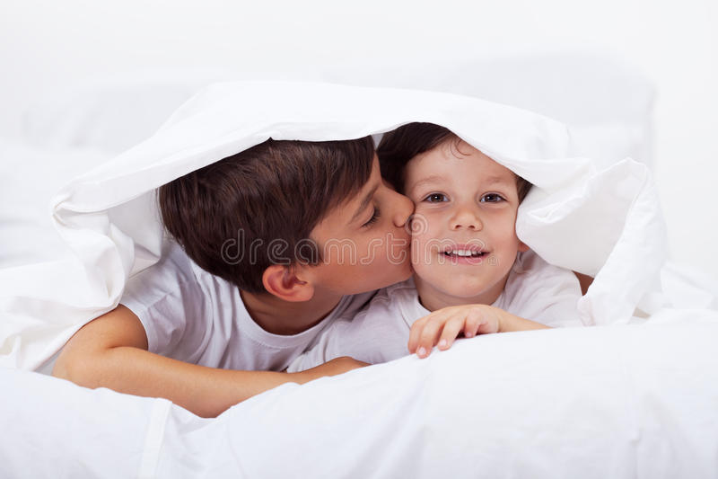 Kids playing under the quilt stock photography