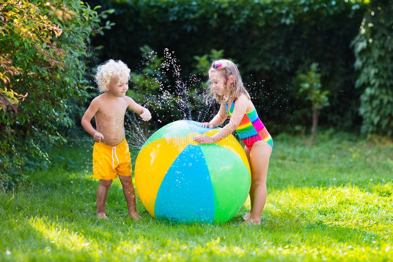 Kids playing with water ball toy. Child playing with toy ball garden sprinkler. Preschooler kid run and jump. Summer outdoor water fun in the backyard. Children royalty free stock photo