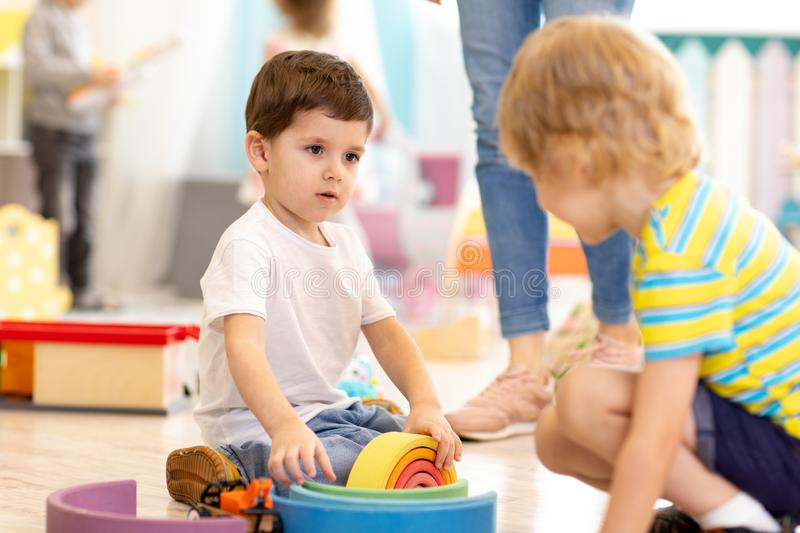 Kids playing wooden toys in kindergarten or nursery stock images