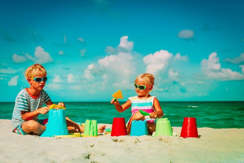 Kids- pojke- och flickalek med leksaker på sandstranden arkivfoto