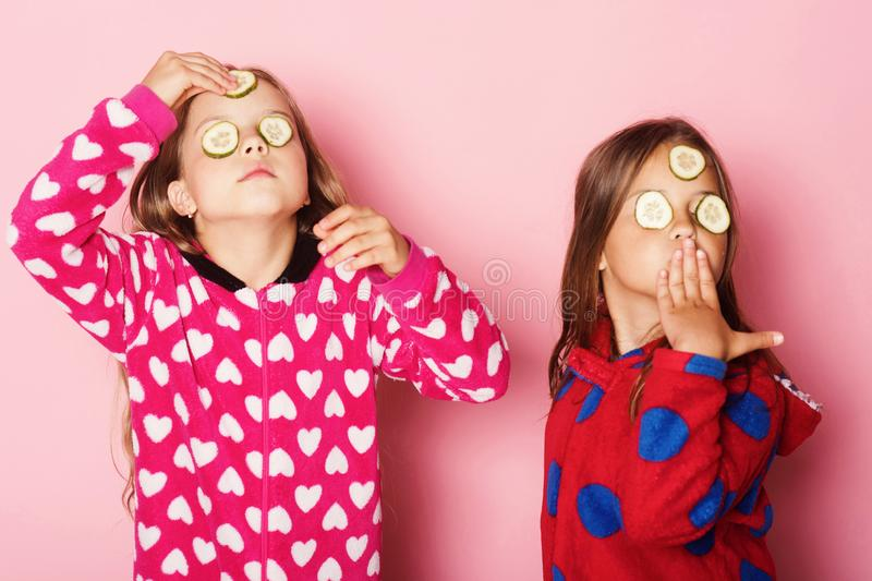 Kids pose on pink background. Children with proud faces. Cucumbers on eyes and loose hair have fun. Girls in colorful polka dotted pajamas. Childhood royalty free stock photos