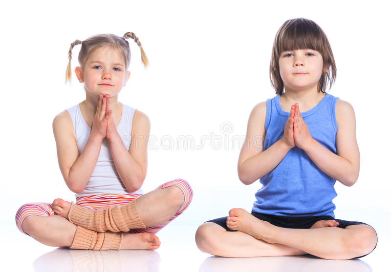 Kids practice yoga. Cute little boy and girl practice yoga. Isolated on the white background royalty free stock photography