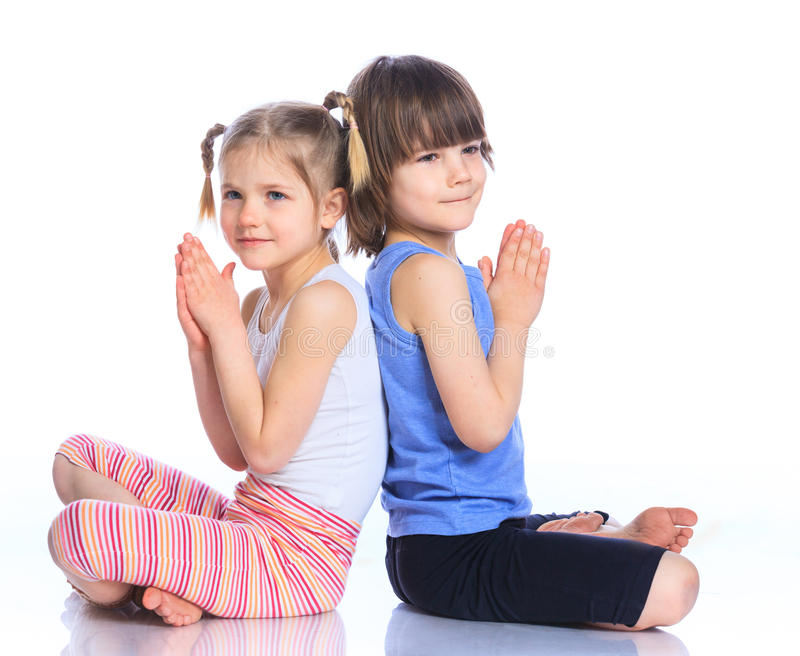 Kids practice yoga. Cute little boy and girl practice yoga. Isolated on the white background royalty free stock images
