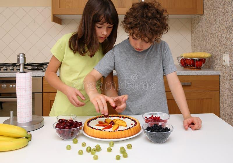 Kids preparing fruity cake royalty free stock images