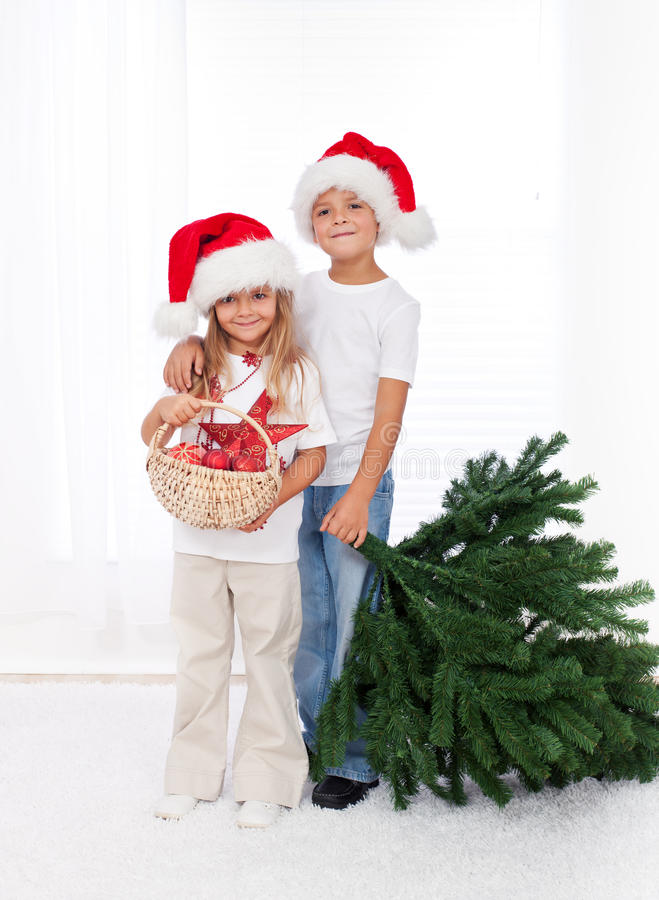 Kids preparing to decorate the christmas tree. Kids wearing santa hats preparing to decorate the christmas tree - getting the props together royalty free stock images