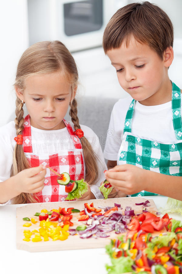 Kids preparing veggies on stick. In the kitchen - healthy nutrition concept stock photography