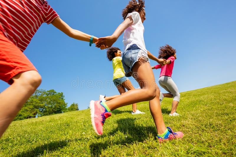 Kids in profile run and pull hands of each other. Profile view of kids run and pull each other in the park holding hands  on legs stock image