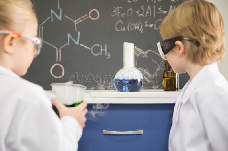 Kids in protective glasses and lab coats making experiment in chemical laboratory. In laboratory royalty free stock images