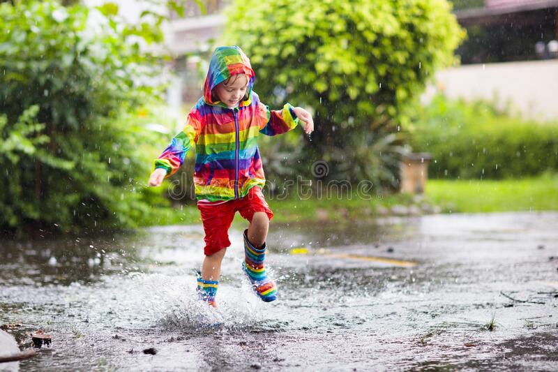Kids in puddle in autumn rain. Waterproof wear stock images