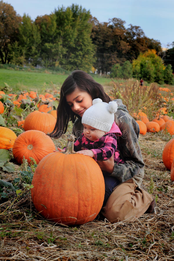 Kids in pumpkin patch. A cute baby wearing a white sock hat and an older tween sister are in a pumpkin patch behind a very large pumpkin. Shallow depth of field stock photos