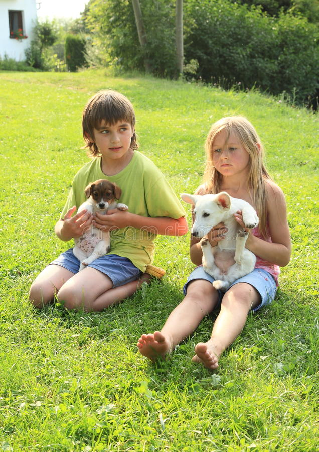 Kids with puppies. Kids - little boy and sad barefoot girl playing with dogs - puppies royalty free stock photo