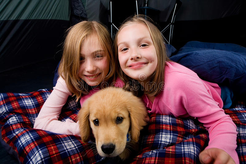 Kids and a puppy in a tent stock photography