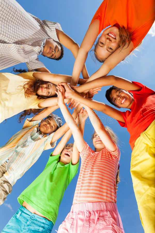 Kids put arms in star shape on sky background stock photos