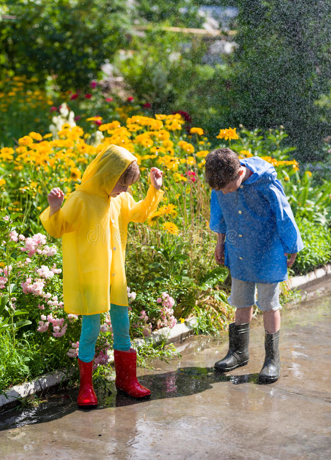 Kids in rain. At backyard royalty free stock photos