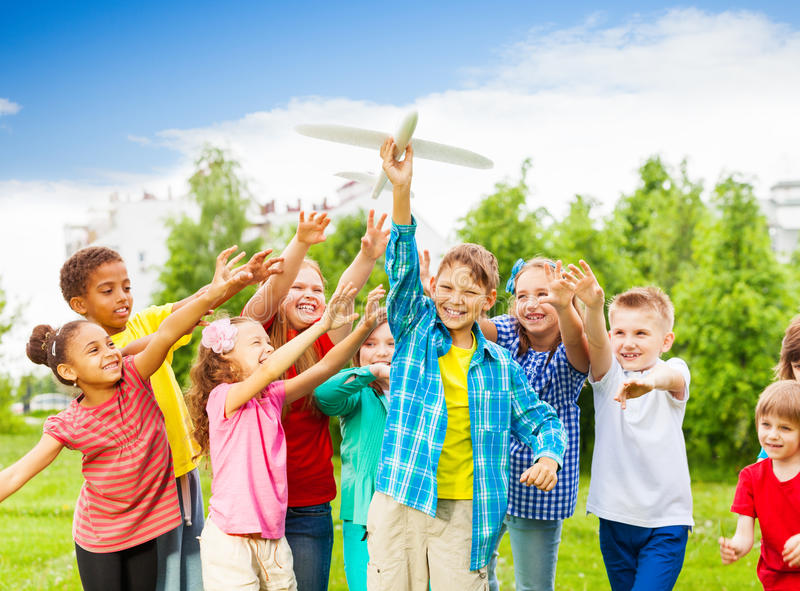 Kids reaching after white airplane toy with arms. Kids reaching after big white airplane toy with arms standing close in the field during summer day stock images