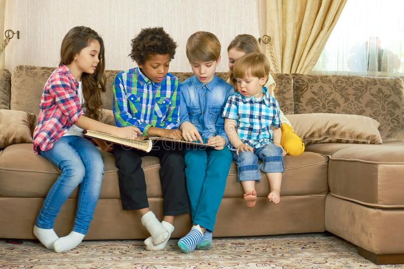 Kids reading a book indoors. Children sitting in the room royalty free stock images