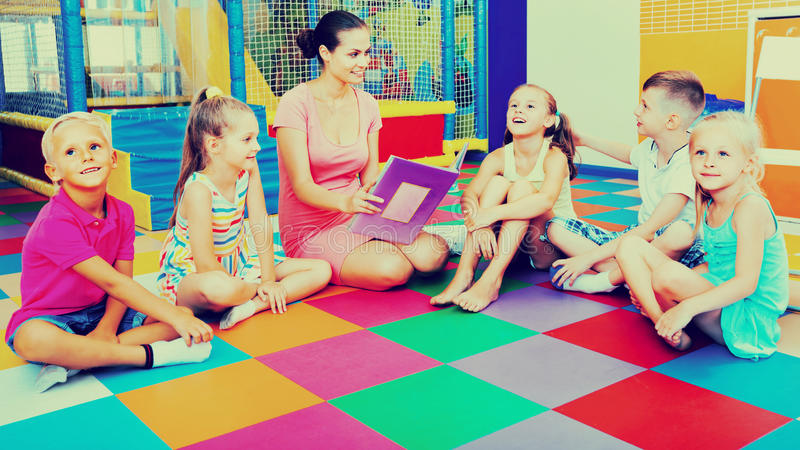Kids reading book with teacher at school class stock images