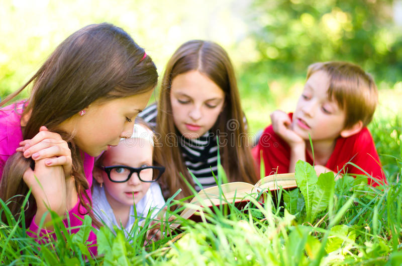Kids reading a book. Kids reading together enjoying a book laying on the grass outdoors royalty free stock image