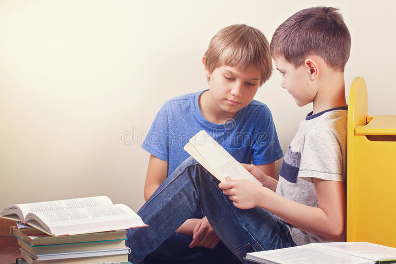 Kids reading books at home stock photos