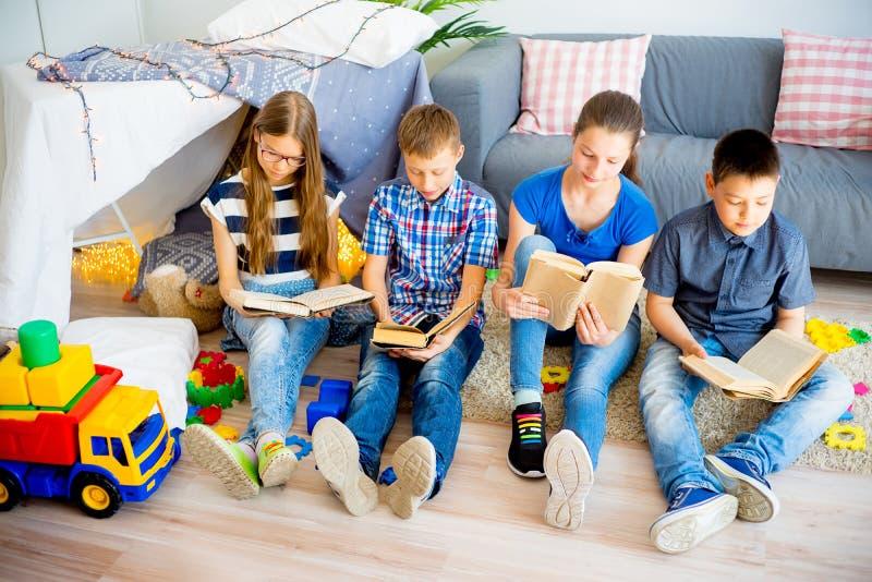 Kids reading books. Row of kids reading books on carpet stock images