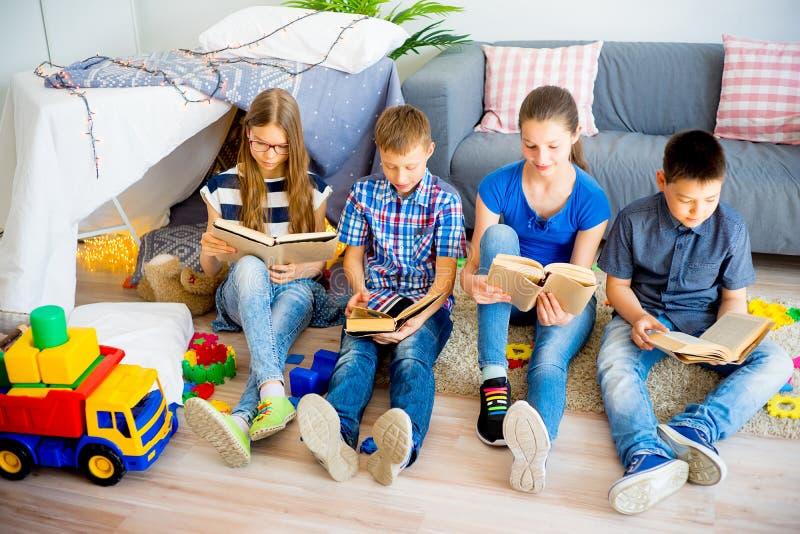Kids reading books. Row of kids reading books on carpet royalty free stock image