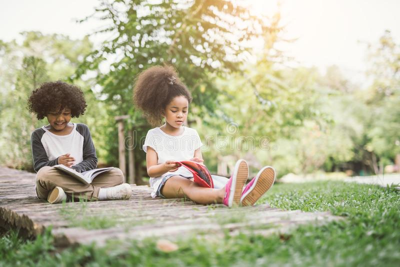 Kids reading with friend. Little Afro child girl reading book between green spikes meadow garden with friend read education concept royalty free stock images