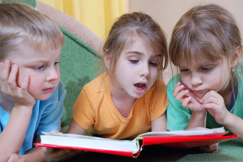 Kids reading the same book. Group of 5 year old kids reading their first real thick book themselves stock photos