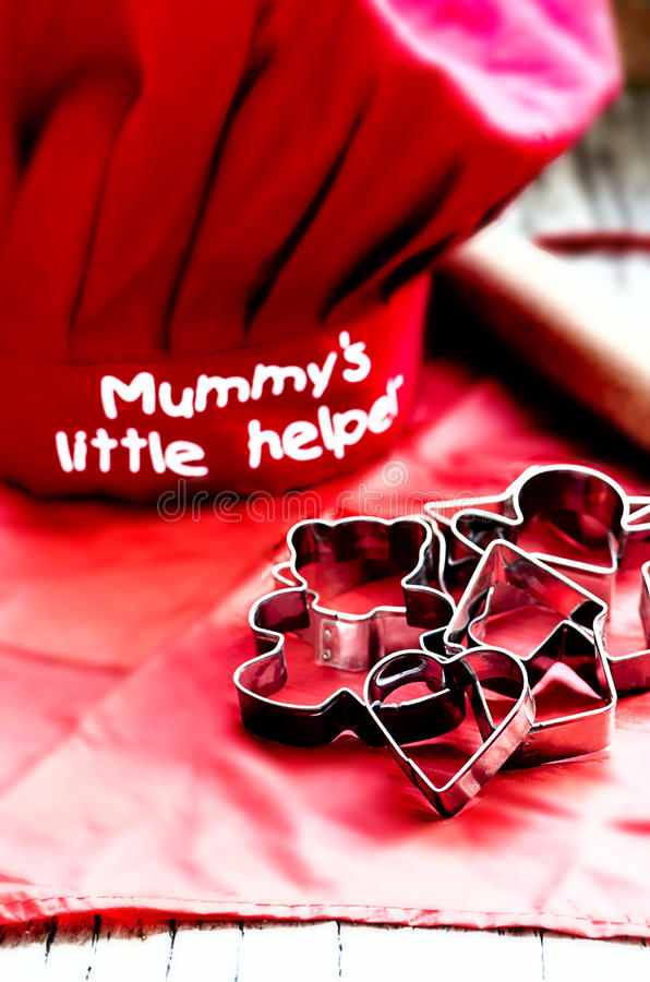 Kids red toque and apron, cookie cutters and wooden rolling pin stock photos