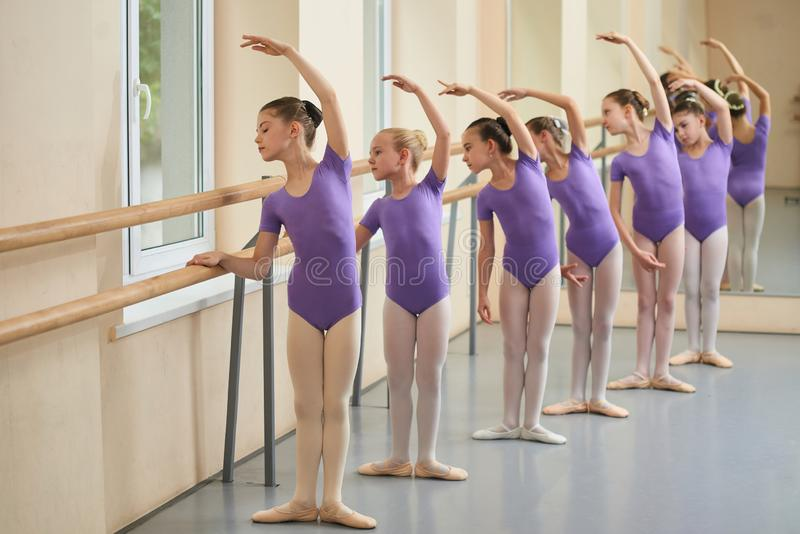Kids rehearsing at ballet dance school. Group of girls practicing ballet at ballet barre. Childrens ballet school royalty free stock image