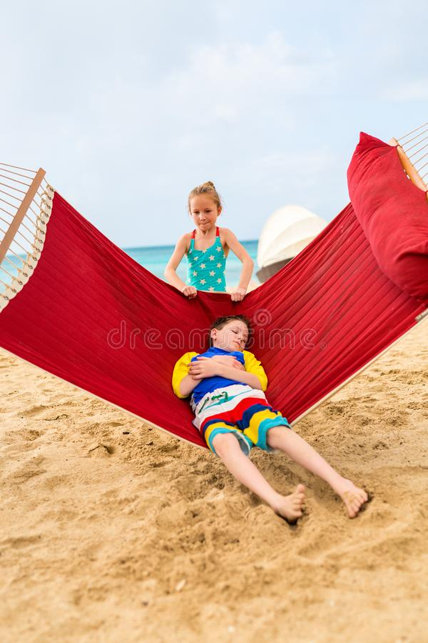 Kids relaxing in hammock. Brother and sister kids relaxing in hammock at tropical beach stock photos