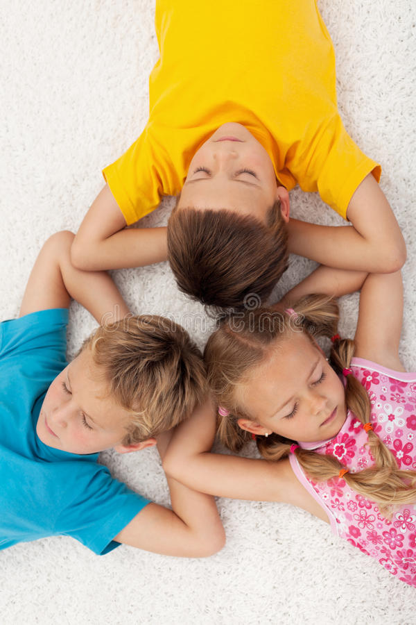 Kids relaxing and meditating. Three kids relaxing and meditating on the floor stock photos