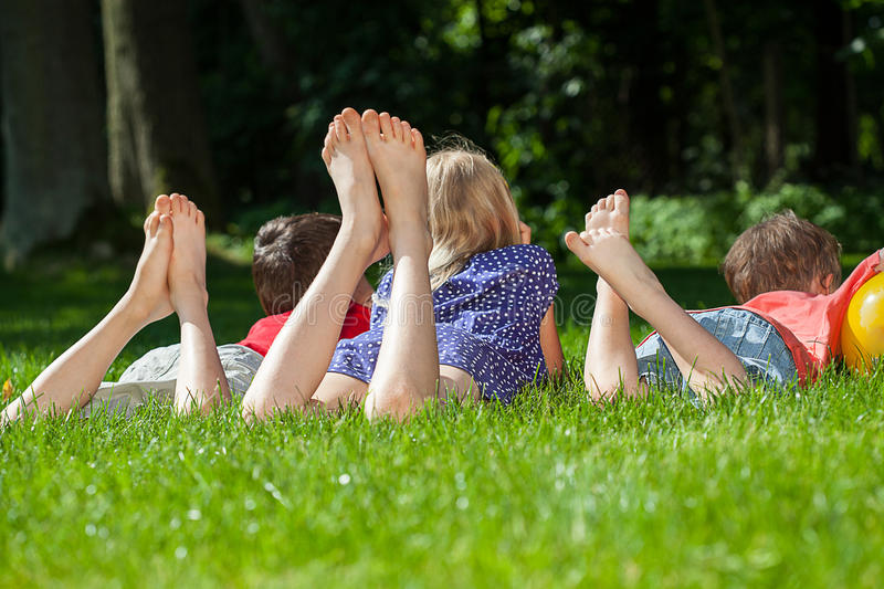 Kids relaxing in park. Three kids relaxing the park on the grass royalty free stock photos