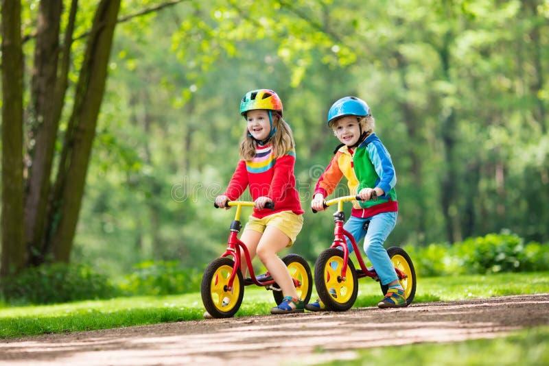 Kids ride balance bike in park. Children riding balance bike. Kids on bicycle in sunny park. Little girl and boy ride glider bike on warm summer day. Preschooler royalty free stock photo