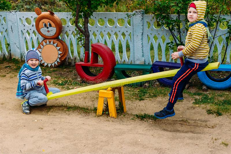 Kids ride a swing in the playground royalty free stock photos