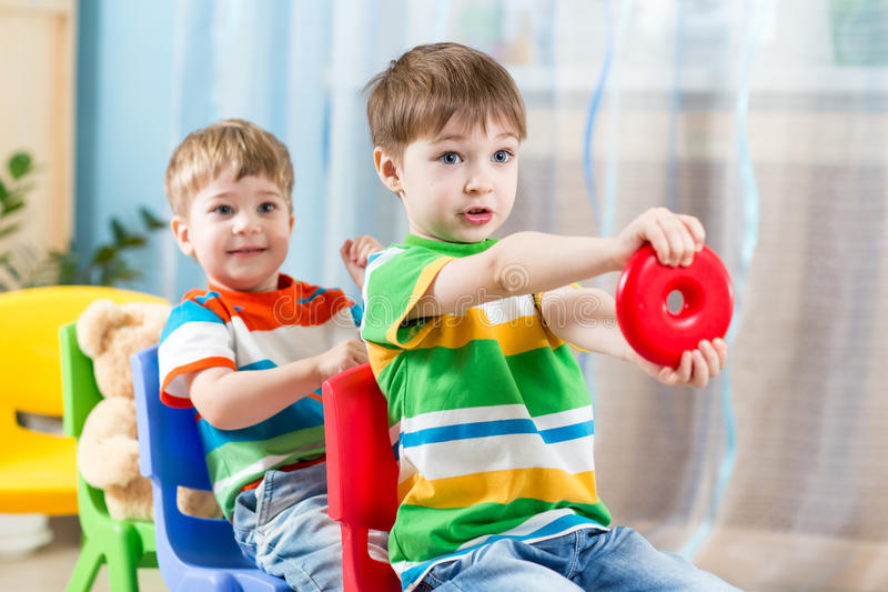 Kids riding on carriages made from chairs royalty free stock photos