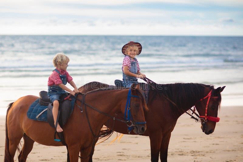 Kids riding horse on beach. Children ride horses royalty free stock photos
