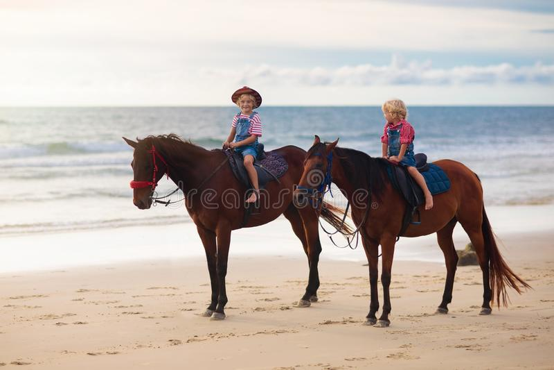 Kids riding horse on beach. Children ride horses stock photo