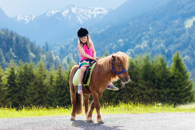 Kids riding pony. Child on horse in Alps mountains royalty free stock image
