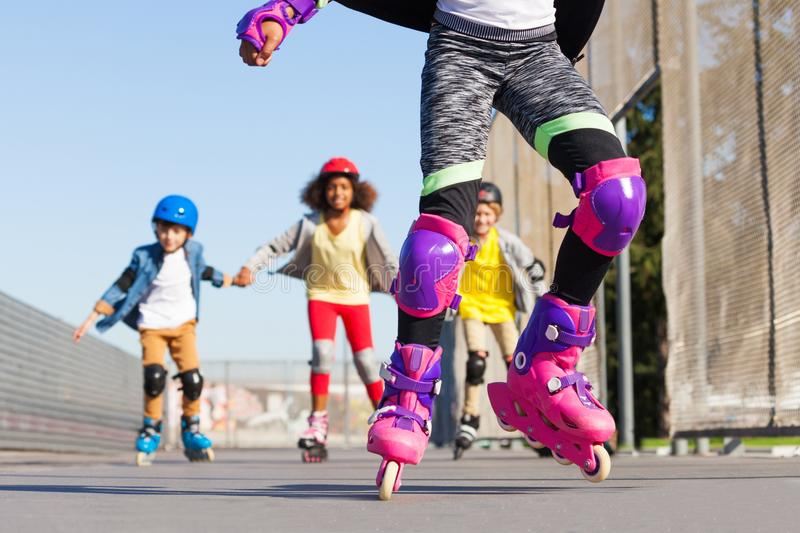 Kids rollerblading in protective gear outdoors. Kids in roller helmets, knee and elbow pads for safe rollerblading outdoors royalty free stock images