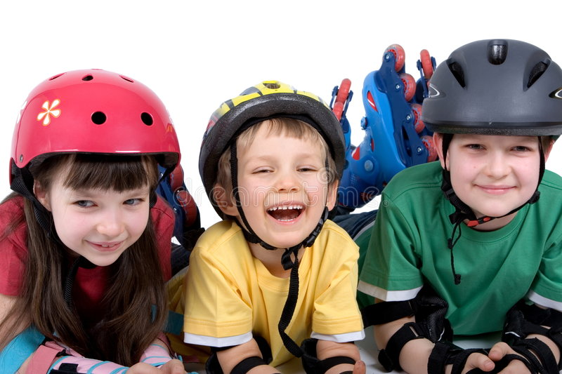 Kids with rollerblades. Three happy, delightful kids, having fun and wearing safety helmets and elbow pads as they lie on the floor while roller-blading stock photo
