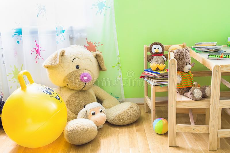 Kids Room Interior with Wooden Furniture Set. Teddy Bear on Chair Big Plush Toys Books Crayons on Table. royalty free stock photo