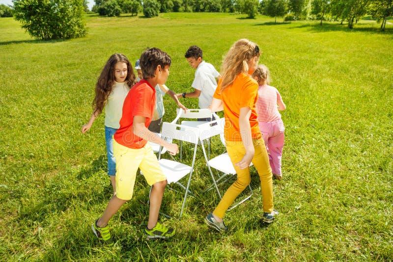 Kids run around playing musical chairs game. Kids run around chairs playing a game outside in summer period royalty free stock photos